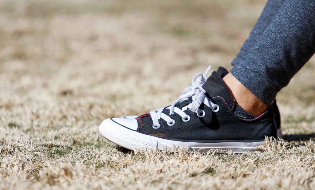 Fuß mit Schwarzem Schuh (Chuck) mit weißen Schnürsenkel im verbrannten Gras