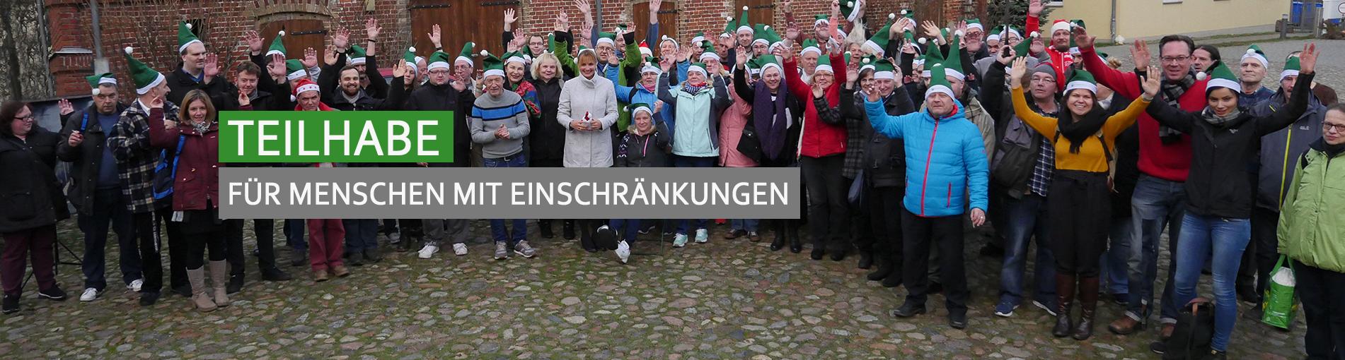 """Gruppenfoto von Klienten vor einer alten Scheune auf dem Hönower Bauernhof. Alle reißen die Arme in die Luft und haben grüne Weihnachtsmützen auf. Auf dem Bild steht in weißen Buchstaben """"Teilhabe"""" auf einem grünen Balken. Darunter """"Für Menschen mit Einschränkungen"""" auf grauem Balken"""