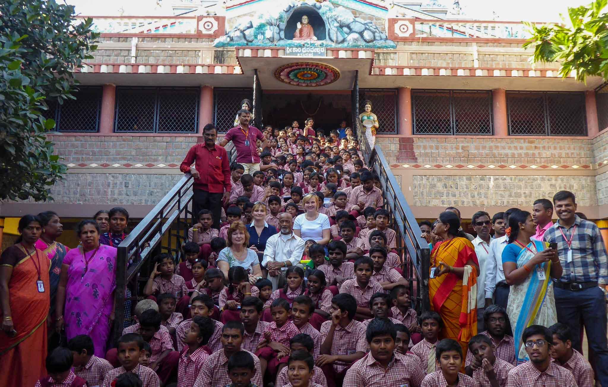 Indien. Viele Menschen sitzen auf einer Treppe vor einem Indischen Gebäude. Alle tragen Schuluniform. In der Mitte der Gruppe sitzen die Geschäftsführerinnen von MITTENDRIN leben e.V. - Internationale Hilfe