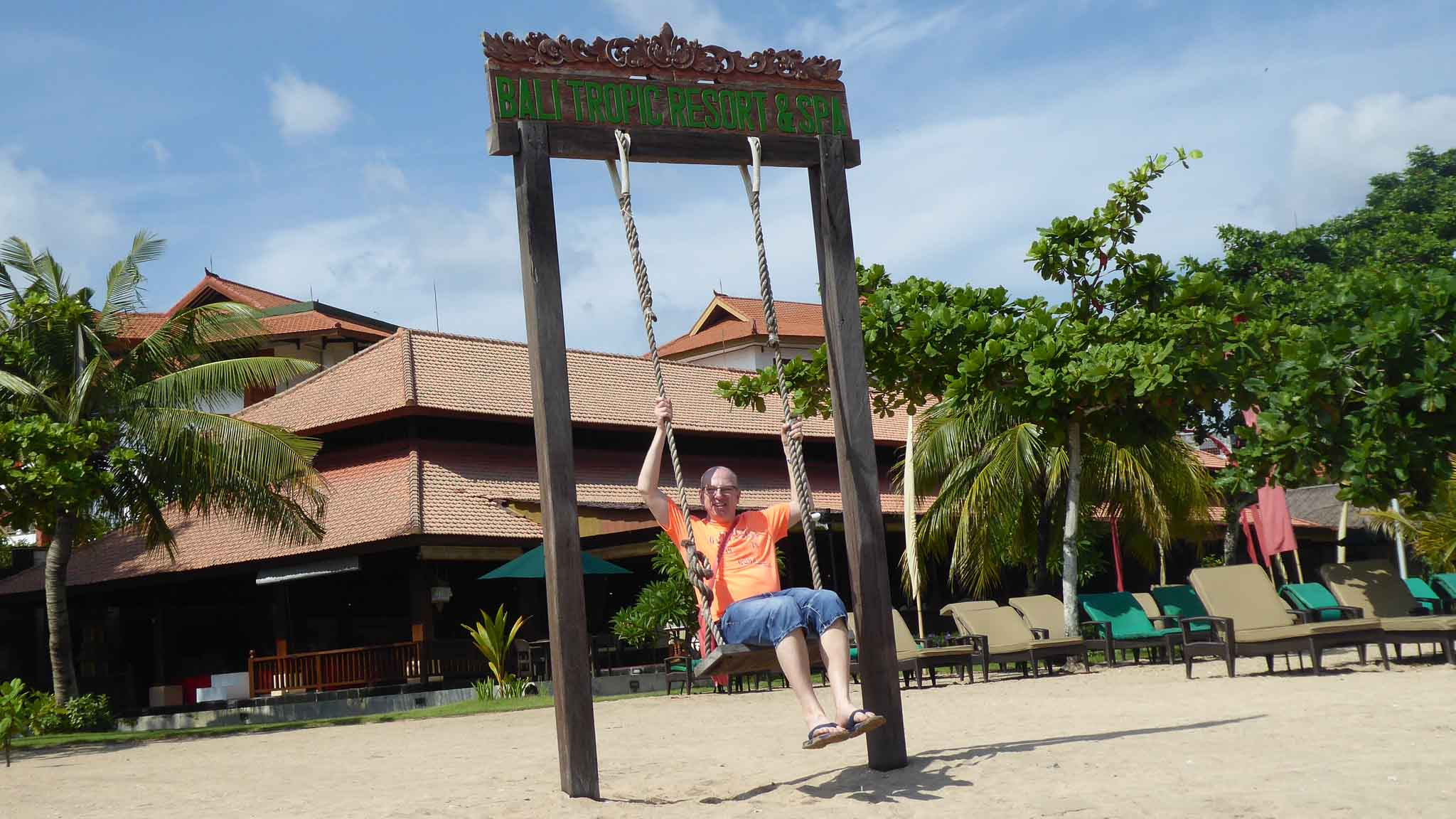 Klientenreise Bali - ein Mann auf einer großen Schaukel am Strand. Im Hintergrund ein Hotel, welches als Tempelanlage gestaltet ist