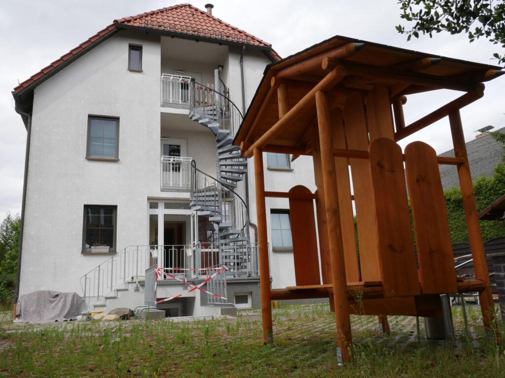 TWG Müllerstraße aus der Froschperspektive weißes Haus mit roten Dach im Hintergrund, davor auf dem Rasen eine Holzbank mit Dach