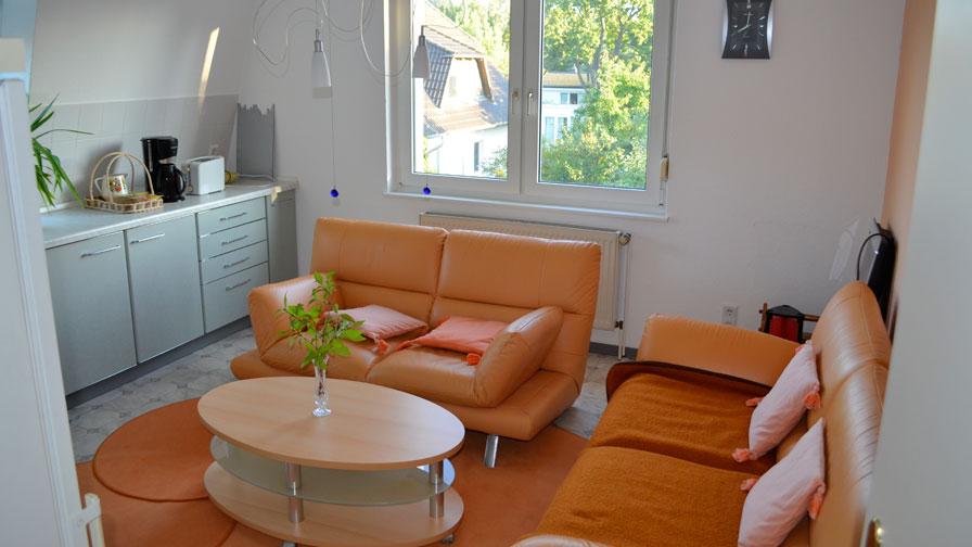 Gemeinschaftraum TWG Rüsternallee - Orangefarbene Couch, weiße Schrankzeile, runder Holztisch