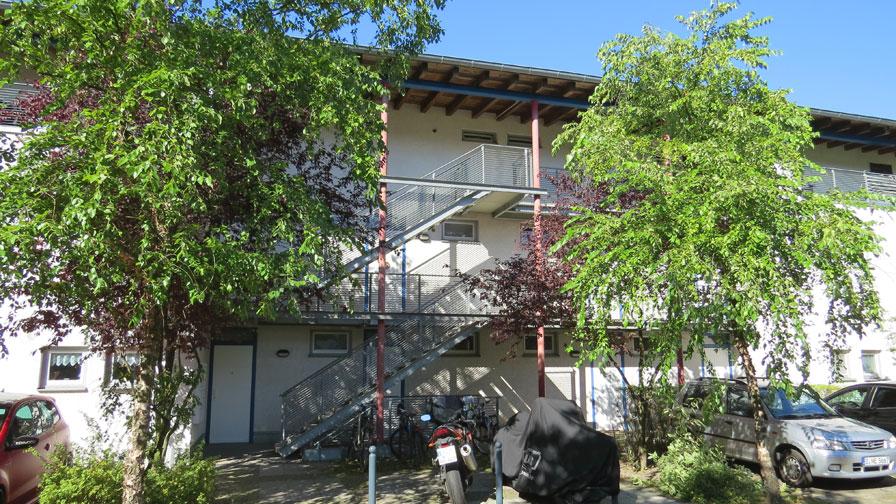 TWG Waldowpark von außen. Wohnhaus mit flachem Dach und hellblauer Fassade. Davor zwei Bäume und parkende Autos