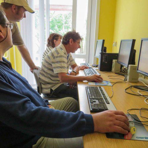 Computerkurs. 3 Personen sitzen an PCS. Der Kursleiter steht dahinter und hilft